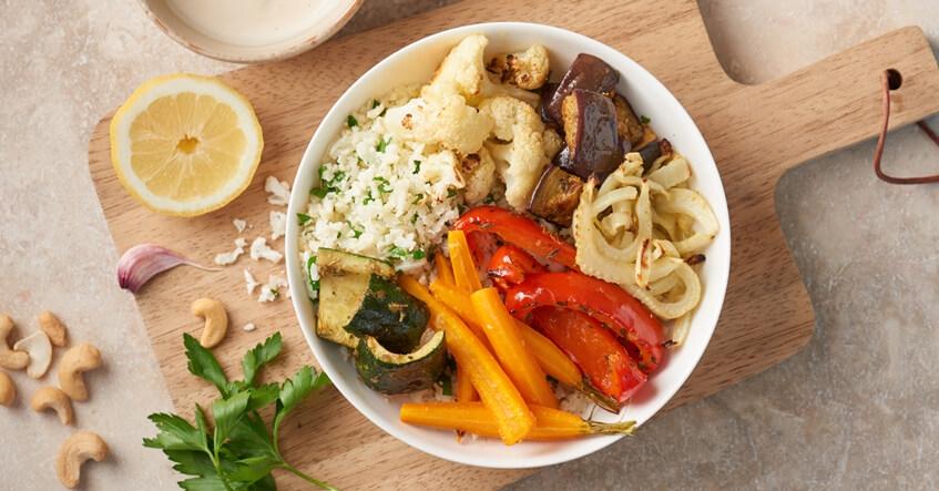 Bowl med grönsaker, blomkålsris och dressing