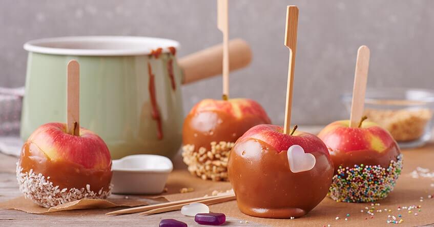 Knäckigt äpple med strössel och kokos doppat i karamell på bakplåtspapper från Toppits