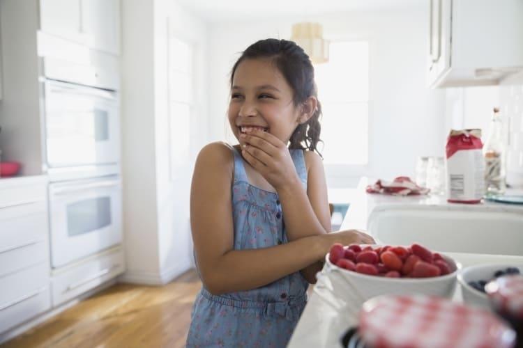 Mamma och barn i köket med jordgubbar